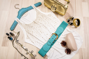 Summer blouse and accessories arranged on the floor.Woman colorful accessories, blue belt, sunglasses and nail polish on a white top with gold rhinestones.