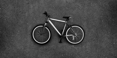 Super large photo of bike lying on the pavement. Bicycle in black and white color. Real asphalt texture background. Best way show postcard with this velo. Velocipede on grey asphault textured surface.