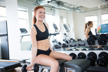 Happy woman lifting weights in gym