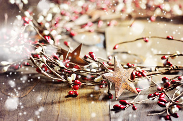 Christmas wreath with red and white berries and rusty metal stars, toned image, selective focus