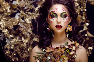 beauty woman with face art and jewelry from flowers orchids close up, creative makeup