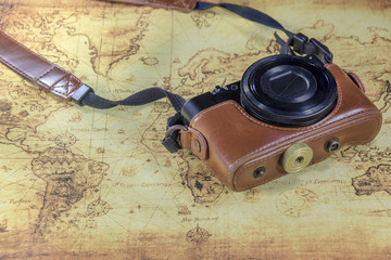 old vintage pocket camera on aold world map