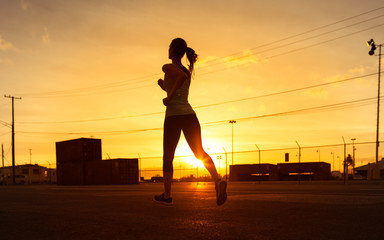 Silhouette of woman running in an industrial city setting