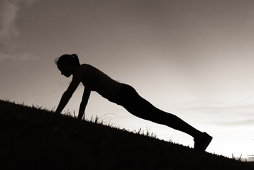 Silhouette of female doing push ups.