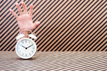 目覚まし時計を捕まえる手