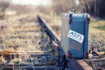 einsamer Koffer auf den Gleisen - Asylpolitik