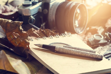 Retro pen on  note pad and old camera on dry leaves in jungle background