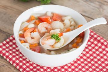 Macaroni with shrimp soup on white bowl.