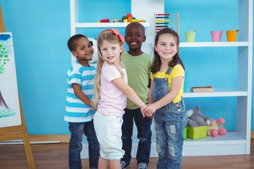 Happy kids holding hands together