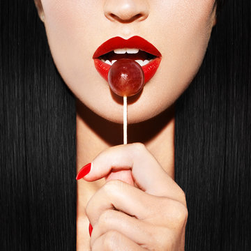 Sexy woman with red lips holding lollipop