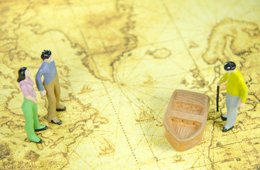 mini model of a man woman and oldman on a old world map