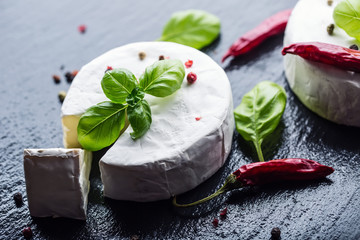 Brie cheese. Camembert cheese. Fresh Brie cheese and a slice on a granite board with basil leaves four colors peper and chili pepers. Italian and Mediterranean ingredients.