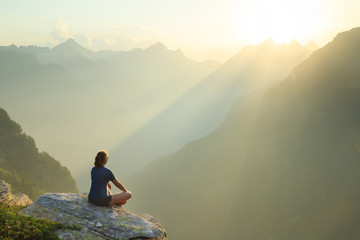 Woman relaxing en enjoying the summer sunset in the mountains.