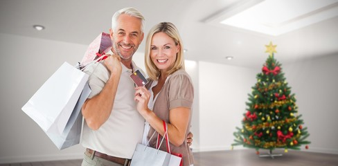 Happy couple with shopping bags and credit card