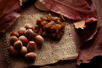 Hazelnuts and raisins with autumn leaves on the background of a
