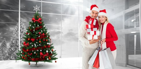 Composite image of happy festive couple with gifts and bags