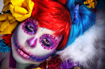 halloween make up sugar skull beautiful model  in bright paper flowers background.