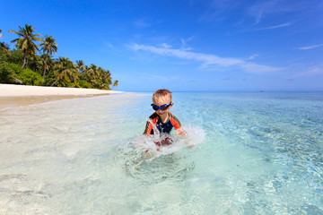 happy little boy swimming on tropical beach