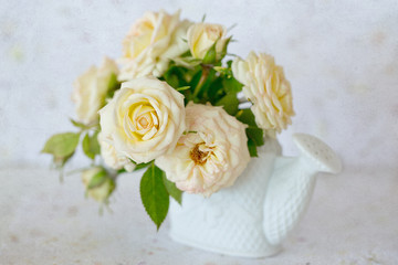 Beautiful fresh cream-colored roses in a vase on a grunge paper background.