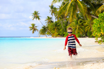 little boy running splashing water on beach