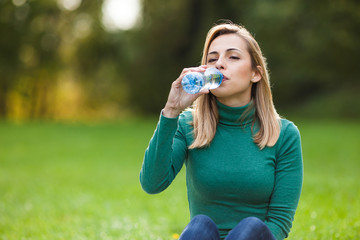 Young woman drinking water in park
