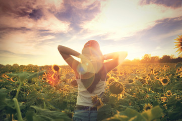 Young woman walking in the field with sunflowers