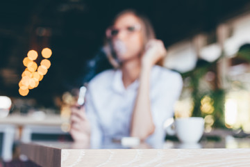 Woman smoking a cigarette in a cafe, blurred background