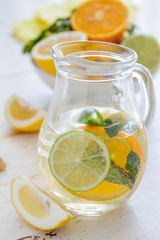 Lemonade and ingredients on white wood background