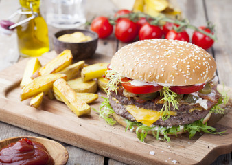 Burger, hamburger with frech fries, ketchup, mustard and fresh vegetables