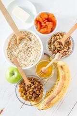 Granola ingredients on white wood background