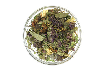 a mixture of herbs in a glass container on a white background