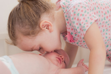 Little girl kissing her newborn brother