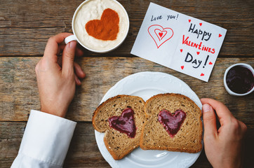 Men's hands hold cup of coffee and a breakfast for Valentine's D