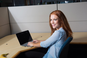 Business woman working on laptop computer in her cubicle