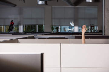 hand raised asking for help in office cubicle