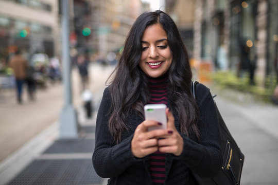 Indian woman in city texting cell phone
