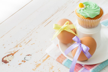 Eggs decorated with ribbon and cupcakes on white wood background