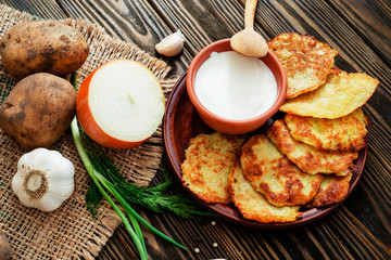 national russian and ukrainian cuisine,  potato pancakes with sour cream , herbs , garlic and spices on a wooden background