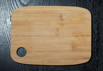 Modern light wooden cutting board with ring hole on a black tabl