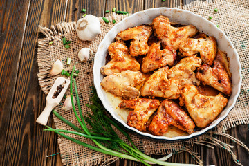 baked chicken wings and garlic marinade with herbs on a wooden background