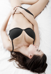 Sexy girl wearing black lingerie and lying on bed