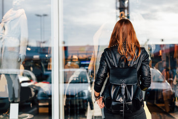 Teen in black in front of shopping windows