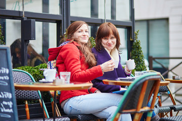 Two girls in Parisian street cafe