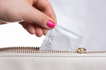 young woman hand with pink nail polish  pulling a white condom from a white leather bag, white background - horizontal