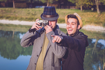 Two friends are taking a photograph outdoor