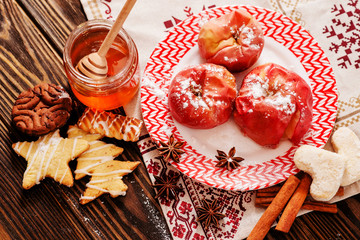 winter dessert , baked apples in powdered sugar , honey , cinnamon , spices and Christmas cookies on a wooden background