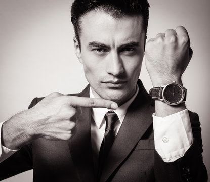 Business man showing time on his wrist watch.