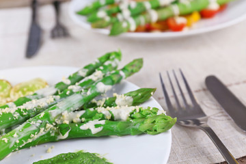 Delicious asparagus dish with onions and green sauce on the table, close up