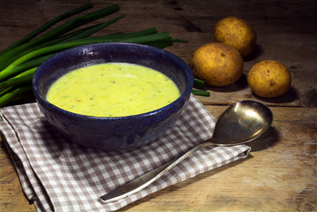 leek cream soup with fresh spring onions and potatoes on rustic