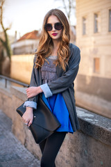 Beautiful fashionable woman holding clutch in the city
